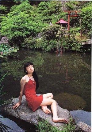 池の岩場で座る美女